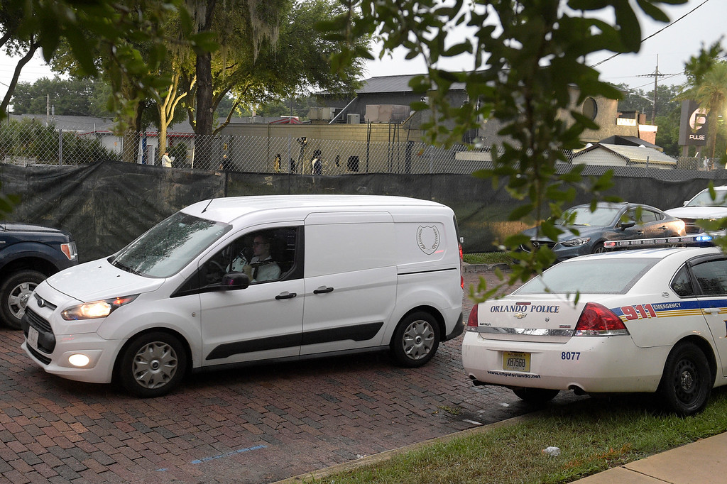 . A van carrying bodies leaves the Pulse nightclub after a shooting involving multiple fatalities at the nightclub in Orlando, Fla., Sunday, June 12, 2016. (AP Photo/Phelan M. Ebenhack)