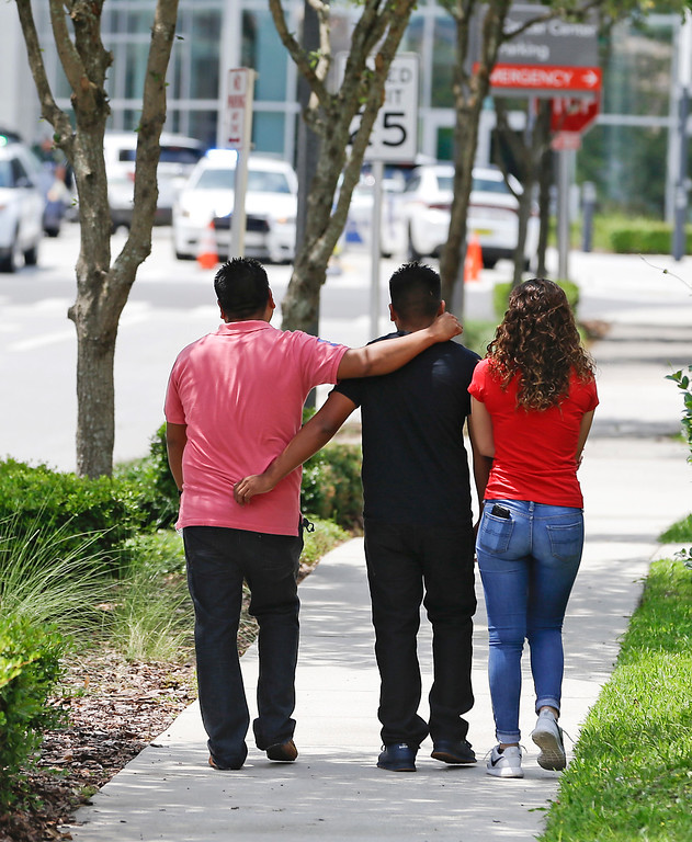 . A group of people walk to the emergency room of Orlando Regional Medical Center after a shooting involving multiple fatalities at a nightclub, Sunday, June 12, 2016, in Orlando, Fla. (AP Photo/John Raoux)