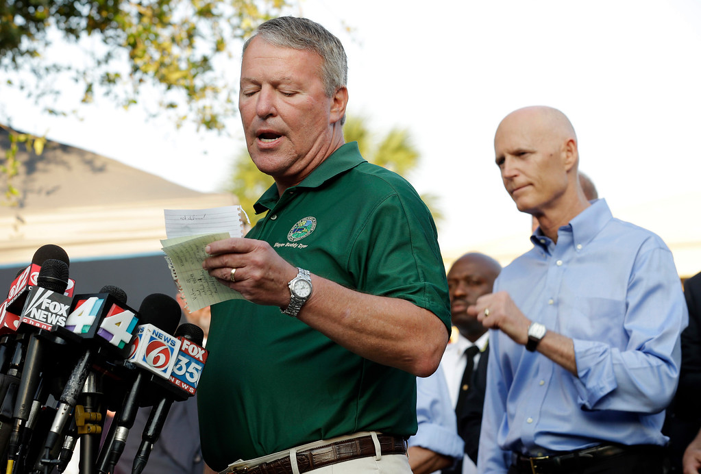 . Orlando, Fla., Mayor Buddy Dyer reads details of the fatal shootings at Pulse Orlando nightclub during a media briefing Monday, June 13, 2016, in Orlando, Fla. Looking on is Florida Gov. Rick Scott at right. (AP Photo/Chris O\'Meara)