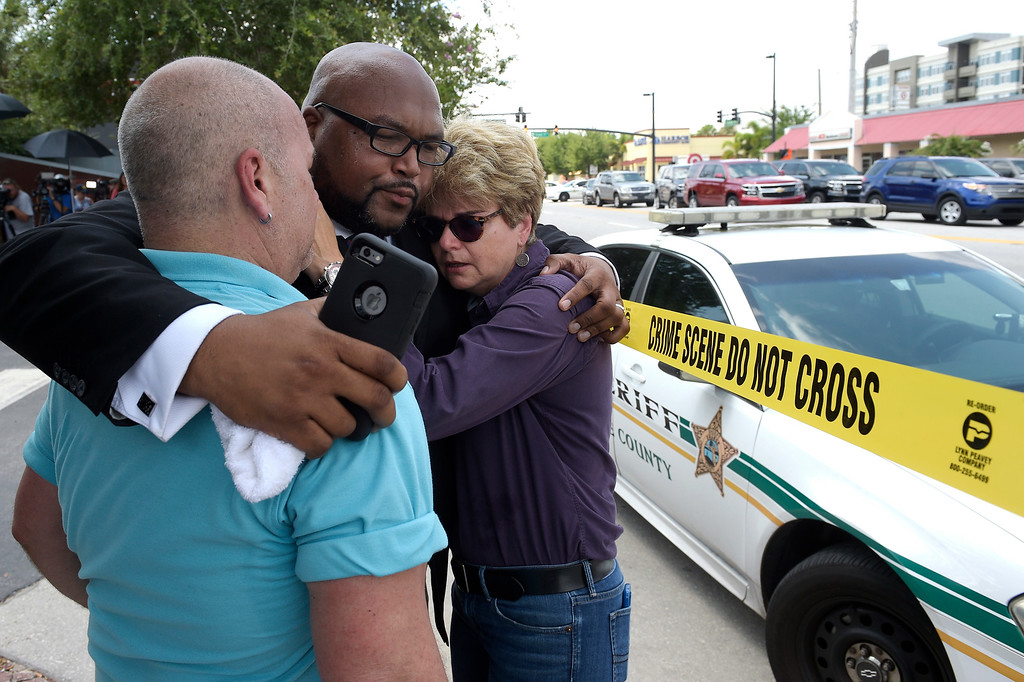 . Terry DeCarlo, executive director of the LGBT Center of Central Florida, left, Kelvin Cobaris, pastor of The Impact Church, center, and Orlando City Commissioner Patty Sheehan console each other after a shooting involving multiple fatalities at a nightclub in Orlando, Fla., Sunday, June 12, 2016. (AP Photo/Phelan M. Ebenhack)