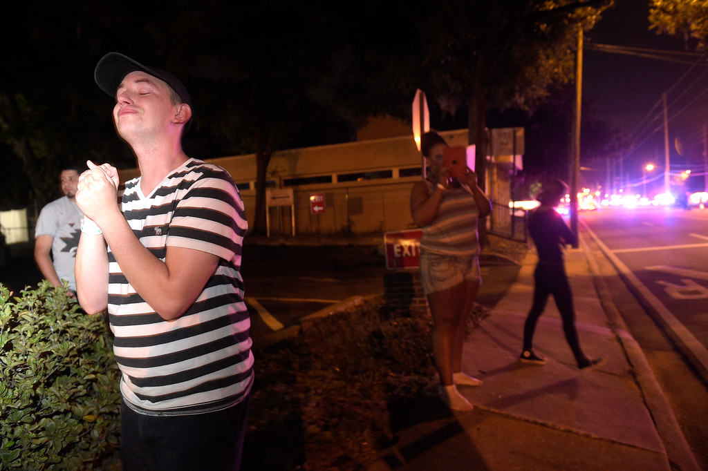. Brandon Shuford, left, waits down the street from the scene of a shooting involving multiple fatalities at a nightclub in Orlando, Fla., Sunday, June 12, 2016. (AP Photo/Phelan M. Ebenhack)