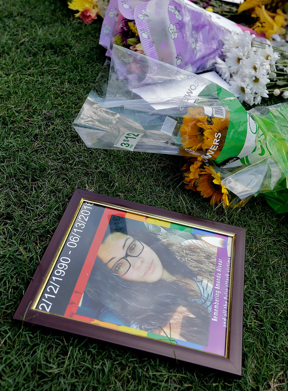 . A photo of Amanda Alvear, one of the victims in the fatal shooting at the Pulse Orlando nightclub, was placed at a makeshift memorial, Monday, June 13, 2016, in Orlando, Fla. (AP Photo/Chris O\'Meara)