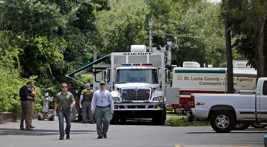 . Law enforcement officials check an apartment complex possibly linked to the fatal shooting at an Orlando nightclub, Sunday, June 12, 2016, in Fort Pierce, Fla. (AP Photo/Alan Diaz)