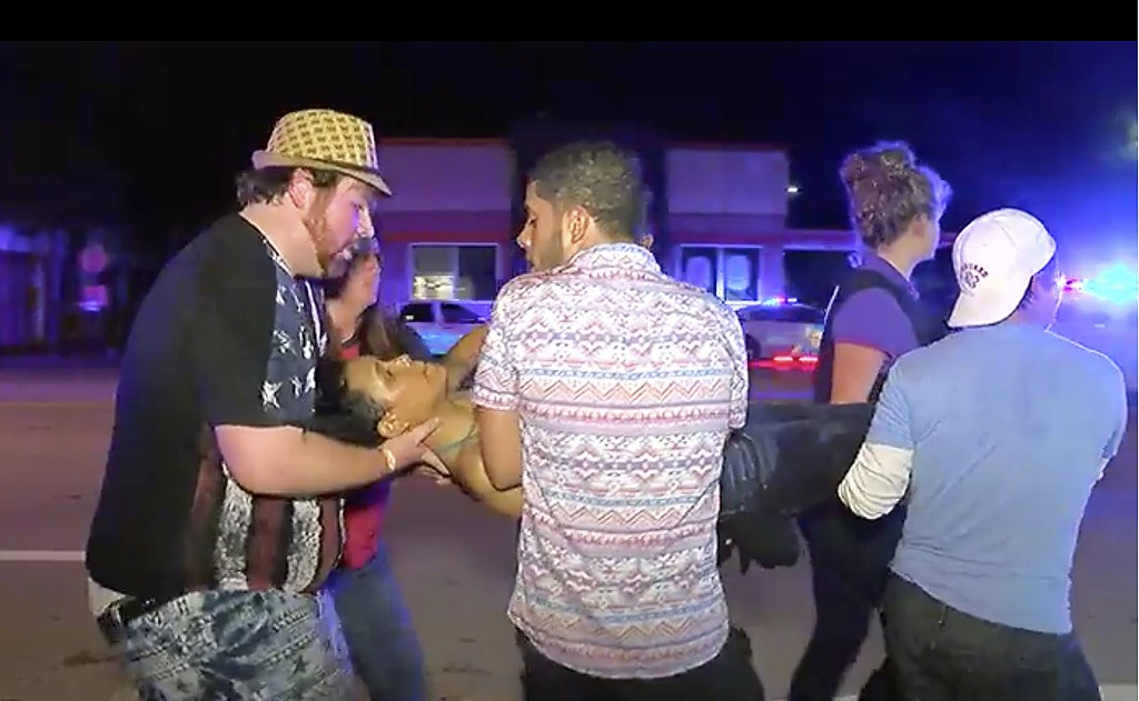. An injured person is escorted out of the Pulse nightclub after a shooting rampage, Sunday morning June 12, 2016, in Orlando, Fla. A gunman wielding an assault-type rifle and a handgun opened fire inside a crowded gay nightclub early Sunday, killing at least 50 people before dying in a gunfight with SWAT officers, police said. It was the deadliest mass shooting in American history. (AP Photo/Steven Fernandez)