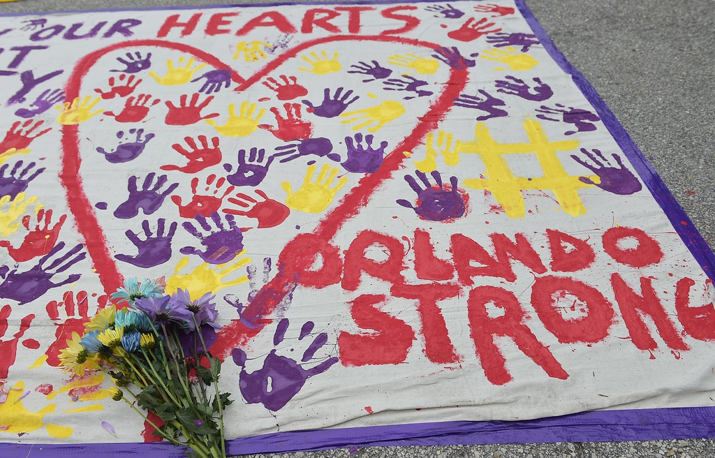 """. A makeshift memorial with flowers and hand prints is seen in a parking lot near the Pulse nightclub in Orlando, Florida on June 12, 2016. A somber President Barack Obama  expressed grief and outrage at the \""""horrific massacre\"""" of 50 late-night revelers at an Orlando gay club, branding it an act of terror and hate. (MANDEL NGAN/AFP/Getty Images)"""