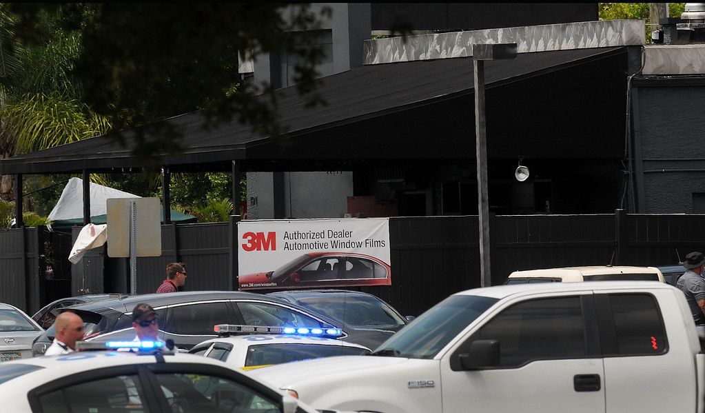 . ORLANDO, FLORIDA - JUNE 12:  Orlando police officers seen outside at the main entrance of Pulse nightclub (black building behind) after a fatal shooting and hostage situation on June 12, 2016 in Orlando, Florida. The suspected shooter, Omar Mateen, was shot and killed by police. 50 people are reported dead and 53 were injured. (Photo by Gerardo Mora/Getty Images)