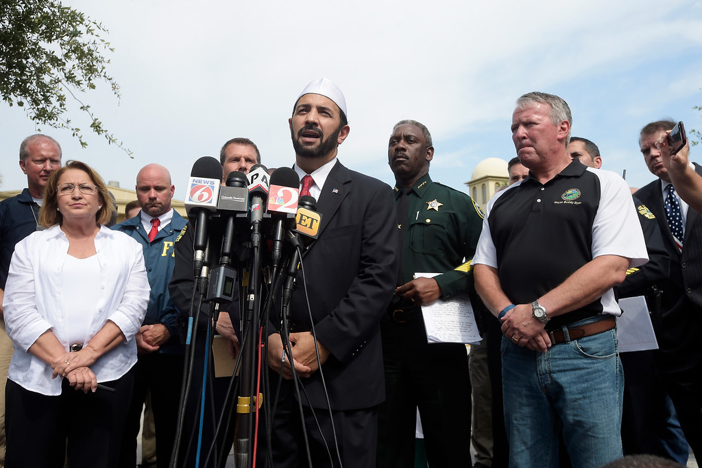 . Imam Muhammad Musri, center, president of the Islamic Society of Central Florida, addresses reporters while flanked by members of law enforcement and community leaders during a news conference after a shooting involving multiple fatalities at a nightclub in Orlando, Fla., Sunday, June 12, 2016. (AP Photo/Phelan M. Ebenhack)