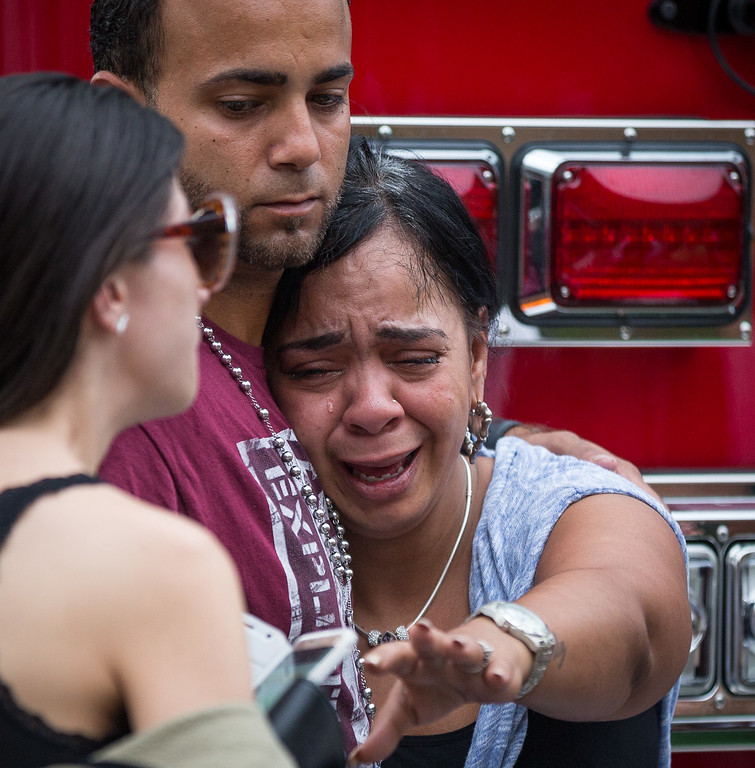 . Friends and family grieve after a list of hospitalized victims was released, implying the death of those who weren\'t on the list and hadn\'t been heard from, outside a Hampton Inn & Suites hotel near the Orlando Regional Medical Center in Orlando, Fla., Sunday, June 12, 2016. A gunman opened fire inside a crowded nightclub early Sunday, before dying in a gunfight with SWAT officers, police said. (Loren Elliott/Tampa Bay Times via AP)
