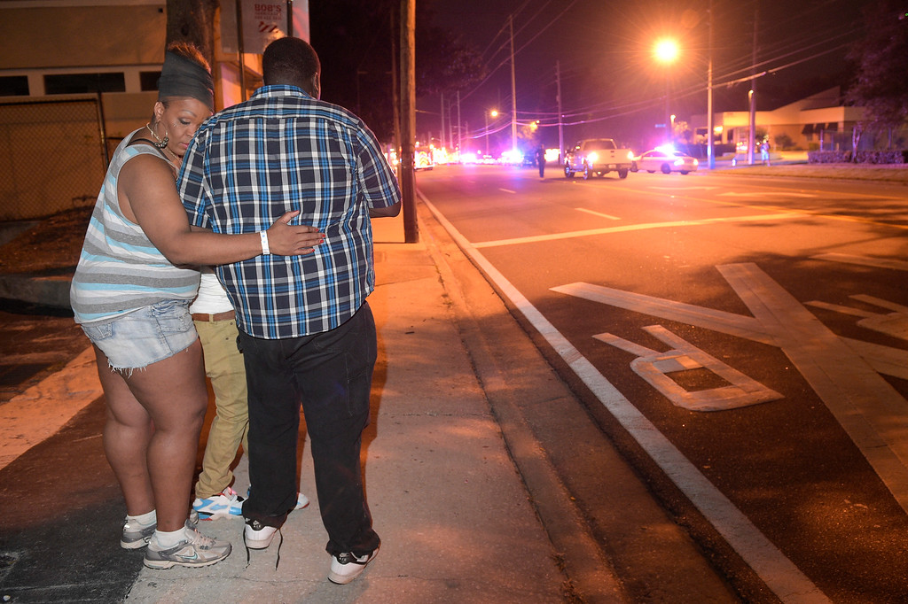 . Bystanders wait down the street from a multiple shooting at the Pulse nightclub in Orlando, Fla., Sunday, June 12, 2016. A gunman opened fire at a nightclub in central Florida, and multiple people have been wounded, police said Sunday.  (AP Photo/Phelan M. Ebenhack)