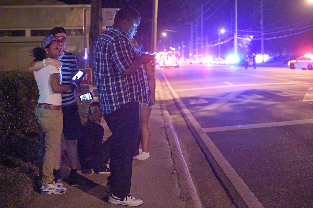 . Jermaine Towns, left, and Brandon Shuford, second from left, wait down the street from the scene of a shooting involving multiple fatalities at a nightclub in Orlando, Fla., Sunday, June 12, 2016. Towns said his brother was hiding in a bathroom at the time. (AP Photo/Phelan M. Ebenhack)