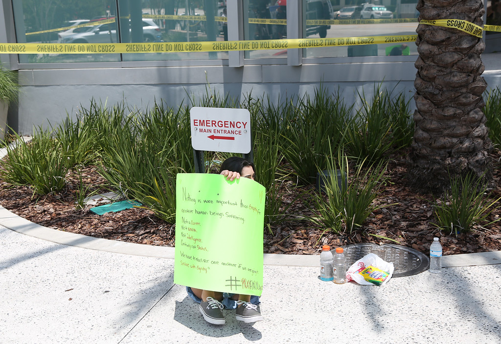 . People hold a vigil outside the Orlando Regional Medical Center in the aftermath of a mass shooting in Orlando, Florida, on June 12, 2016.  Fifty people died and another 53 were injured when a gunman opened fire and seized hostages at the Pulse, a gay nightclub in Orlando, Florida, police said June 12, making it the worst mass shooting in US history. (GREGG NEWTON/AFP/Getty Images)