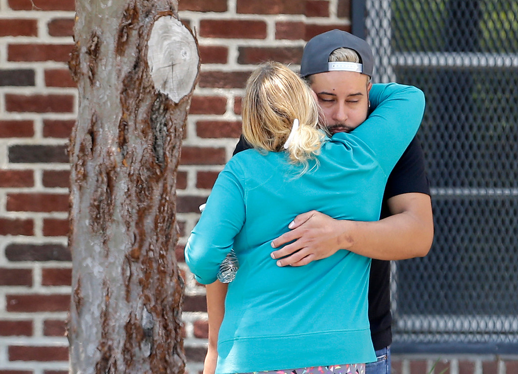 . Family members of victims of the Orlando nightclub shooting hug outside a family reunification center set up at the Beardall Senior Center, Monday, June 13, 2016, in Orlando, Fla. (AP Photo/Alan Diaz)