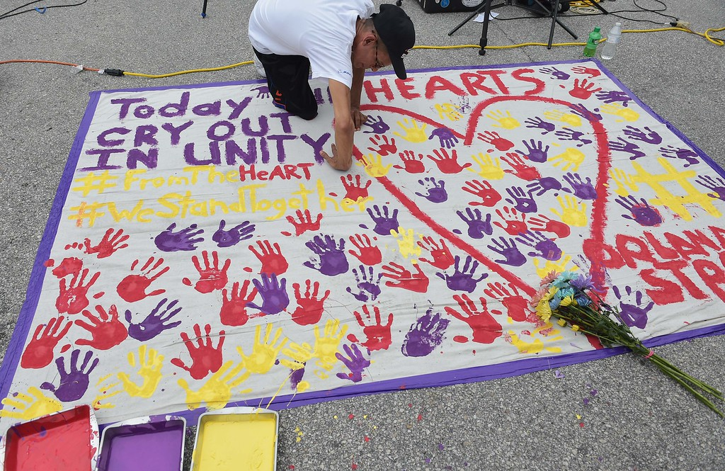 ". A man places a hand print on a makeshift memorial in a parking lot near the Pulse nightclub in Orlando, Florida on June 12, 2016. A somber President Barack Obama  expressed grief and outrage at the ""horrific massacre\"" of 50 late-night revelers at an Orlando gay club, branding it an act of terror and hate. (MANDEL NGAN/AFP/Getty Images)"