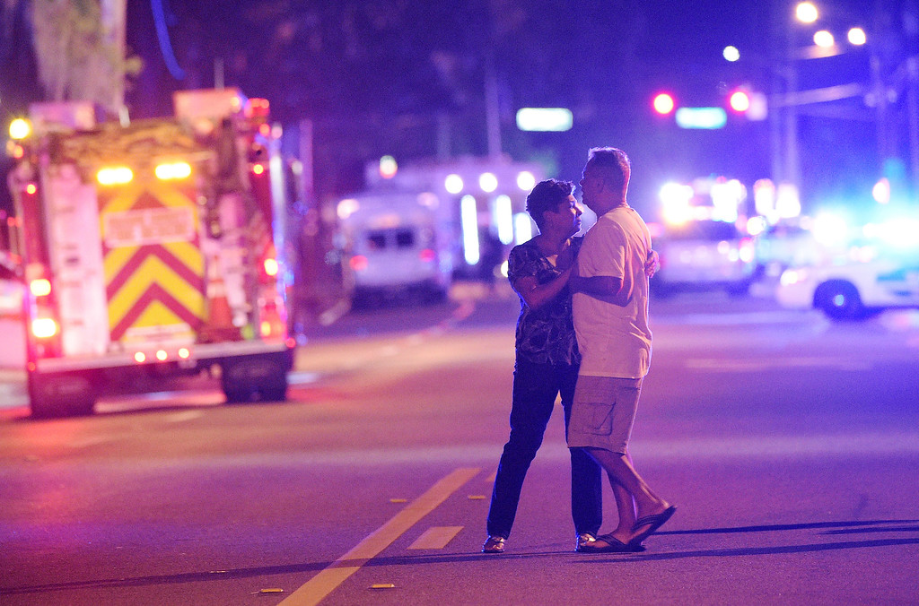 . Family members wait for word from police after arriving down the street from a shooting involving multiple fatalities at Pulse Orlando nightclub in Orlando, Fla., Sunday, June 12, 2016. (AP Photo/Phelan M. Ebenhack)