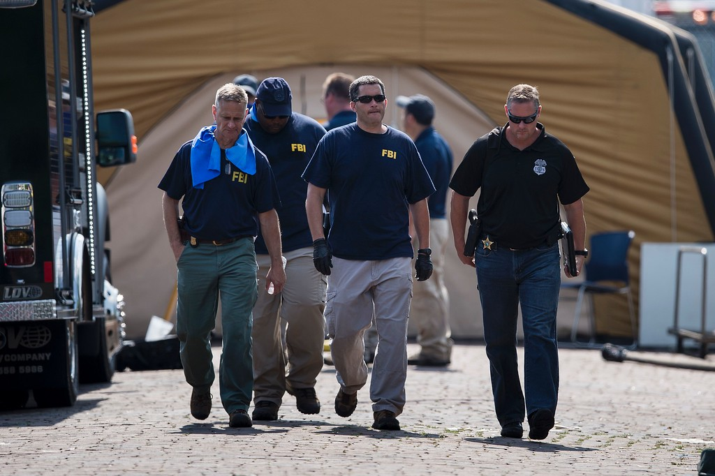 . FBI and other investigators walk from a staging area at the Pulse nightclub June 13, 2016 in Orlando, Florida. Forty-nine people died and more than 50 were injured early June 12 when a heavily-armed gunman opened fire and seized hostages at a gay nightclub in Orlando, Florida, in the worst mass shooting in US history. (BRENDAN SMIALOWSKI/AFP/Getty Images)