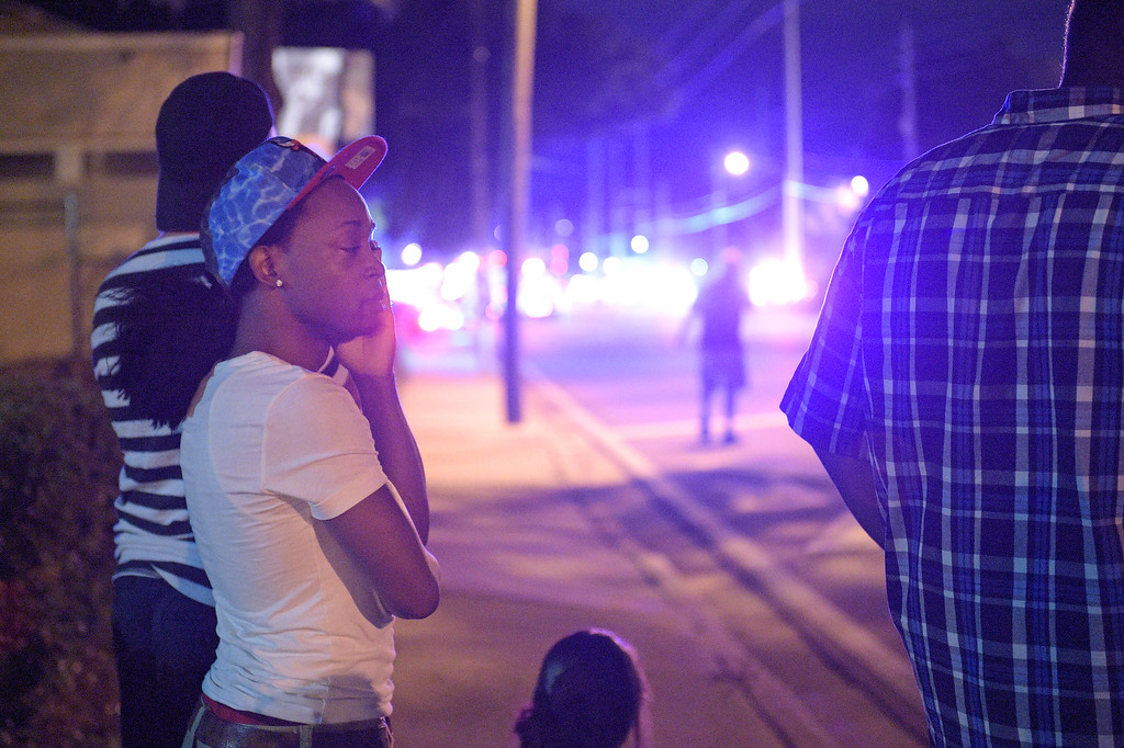 . Jermaine Towns, left, waits down the street from the scene of a shooting involving multiple fatalities at a nightclub in Orlando, Fla., Sunday, June 12, 2016. Towns said his brother was hiding in a bathroom at the time. (AP Photo/Phelan M. Ebenhack)