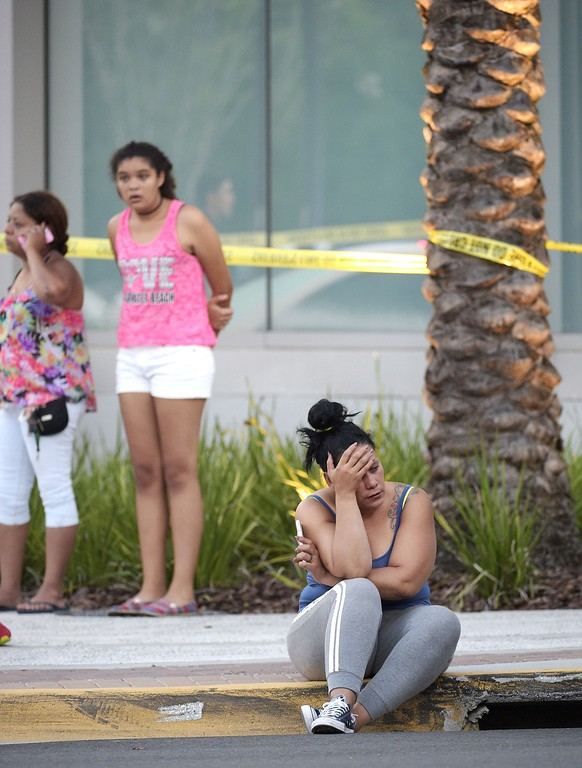 . People wait outside the emergency entrance of the Orlando Regional Medical Center hospital after a shooting involving multiple fatalities at Pulse Orlando nightclub in Orlando, Fla., Sunday, June 12, 2016. (AP Photo/Phelan M. Ebenhack)