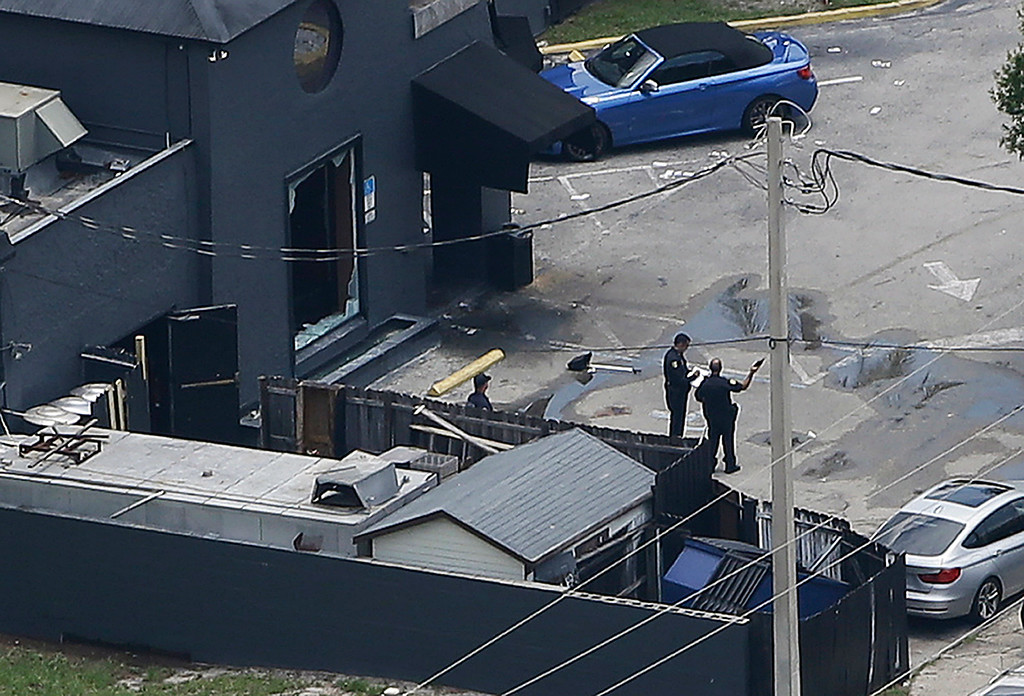 . Law enforcement officials work near a large broken window at the Pulse nightclub following a fatal shooting Sunday, June 12, 2016, in Orlando, Fla. . (AP Photo/Chris O\'Meara)