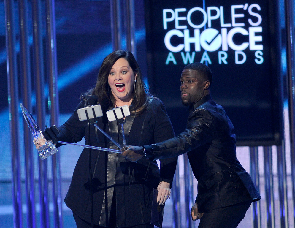 . Kevin Hart, right, films Melissa McCarthy as she accepts the award for favorite comedic movie actress at the People\'s Choice Awards at the Nokia Theatre on Wednesday, Jan. 7, 2015, in Los Angeles. (Photo by Chris Pizzello/Invision/AP)