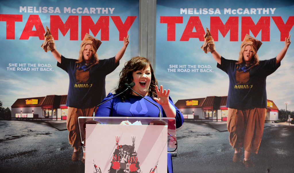 ". Melissa McCarthy, co-writer and star of the new film ""Tammy,\"" takes the stage before getting her hands and feet in cement on Wednesday, July 2, 2014, at the TCL Chinese Theatre in Los Angeles. (Photo by Chris Pizzello/Invision/AP)"