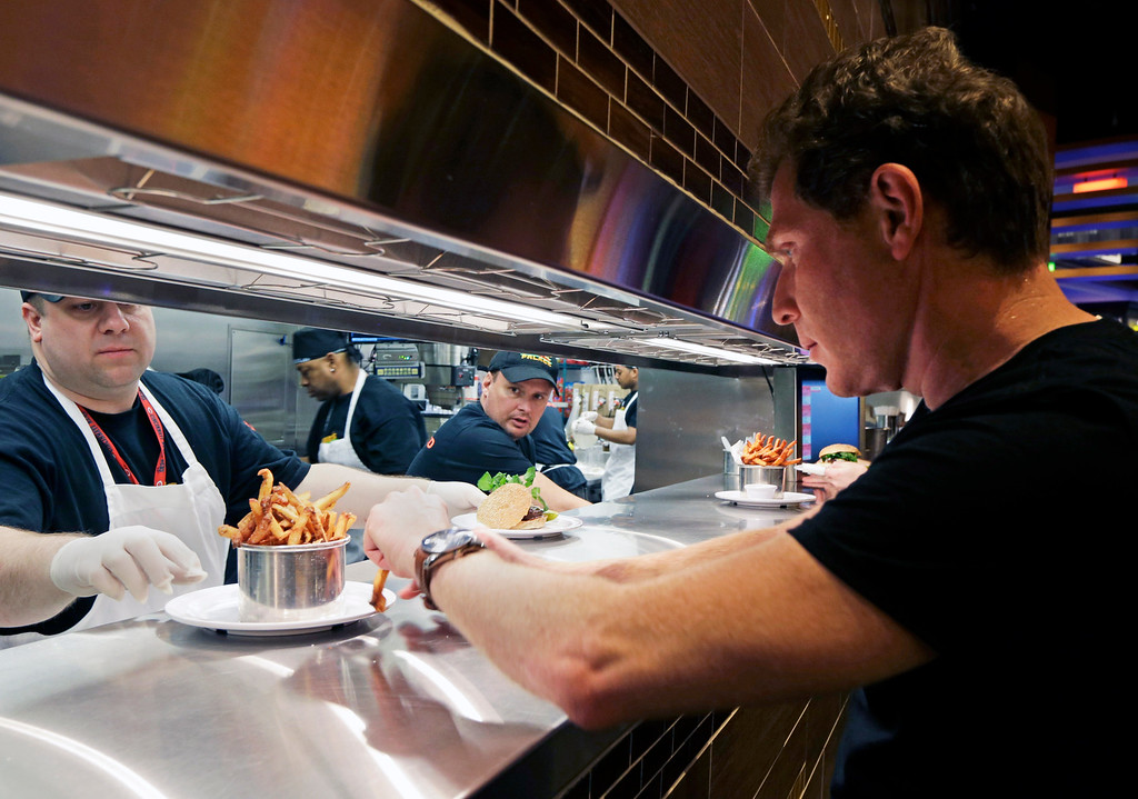 . Chef Bobby Flay, right, checks an order from the kitchen at his new restaurant, Bobby\'s Burger Palace, opening inside Horseshoe Casino Cincinnati, Monday, March 4, 2013, in Cincinnati. The casino is set to open to the public Monday evening. March 4. (AP Photo/Al Behrman)