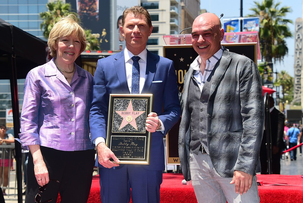 . Chef Bobby Flay poses with Chef Michael Symon (R) and Brooke Johnson (L), President of the Food Network and Cooking Channel during Flay\'s Hollywood Walk of Fame Star ceremony on June 2, 2015, in Hollywood, California. Flay is the first television chef to be accorded the honor.         (FREDERIC J. BROWN/AFP/Getty Images)
