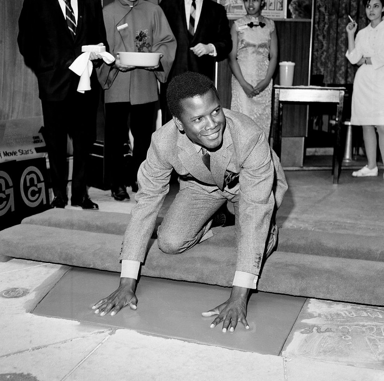 . Actor Sidney Poitier inscribes his signature in wet cement at Grauman?s Chinese Theater in Hollywood, June 23, 1967 after imprinting his hand and footprints in the forecourt of the theater. (AP Photo)
