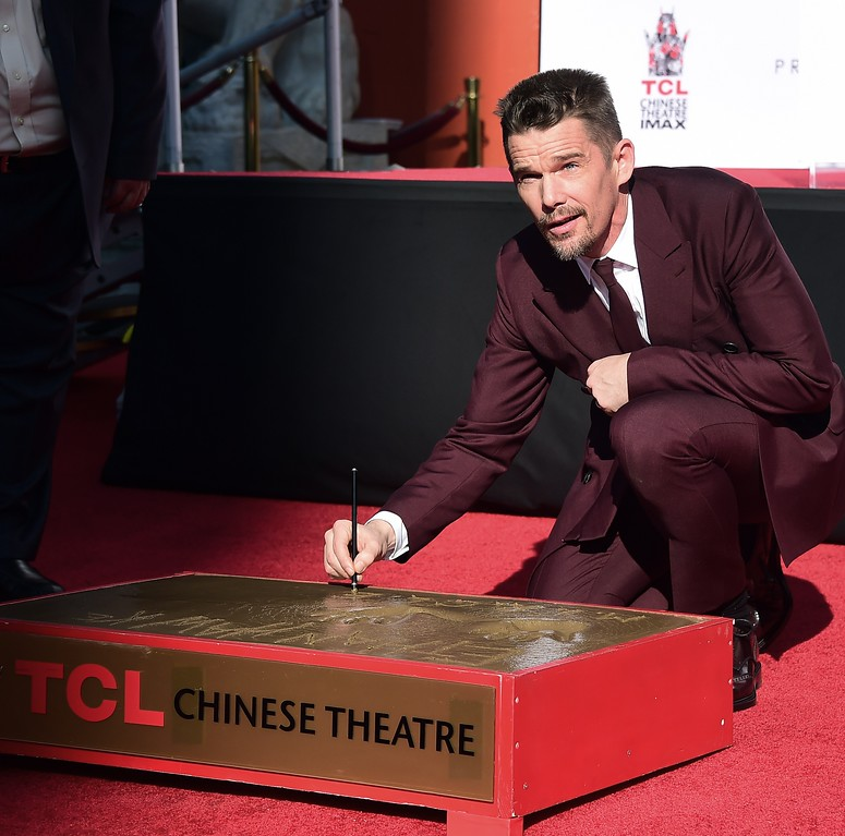 . Actor Ethan Hawke looks up while writing on the cement at a ceremony for his handprints and footprints in front of the TCL Chinese Theater IMAX in Hollywood, California on January 8, 2015. (FREDERIC J. BROWN/AFP/Getty Images)