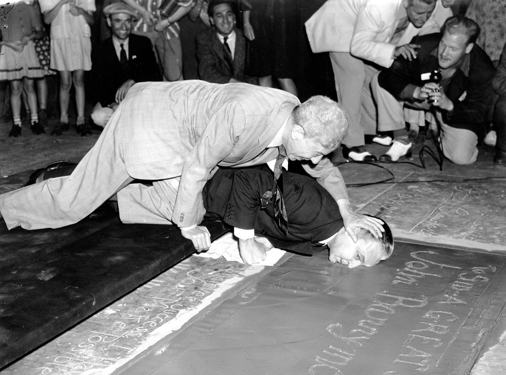 . Stage and film actor John Barrymore plants his face into the wet cement with the assistance of Sid Grauman on the  Hollywood Blvd. sidewalk in front of Mann\'s Chinese Theatre in Hollywood, Calif., on Sept. 5, 1940. Grauman\'s gimmick of having stars put their footprints in cement in front of the movie theatre began in 1927. (AP Photo)