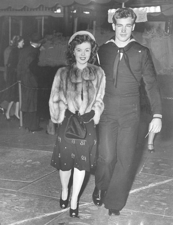 . Shirley Temple, who received a big cheer from the huge crowd of fans who gathered in front of the theater, attends the he 17th Annual Academy Awards with Seaman Don Madison at Grauman\'s Chinese Theater on March 16, 1945.  (Courtesy Los Angeles Public Library)