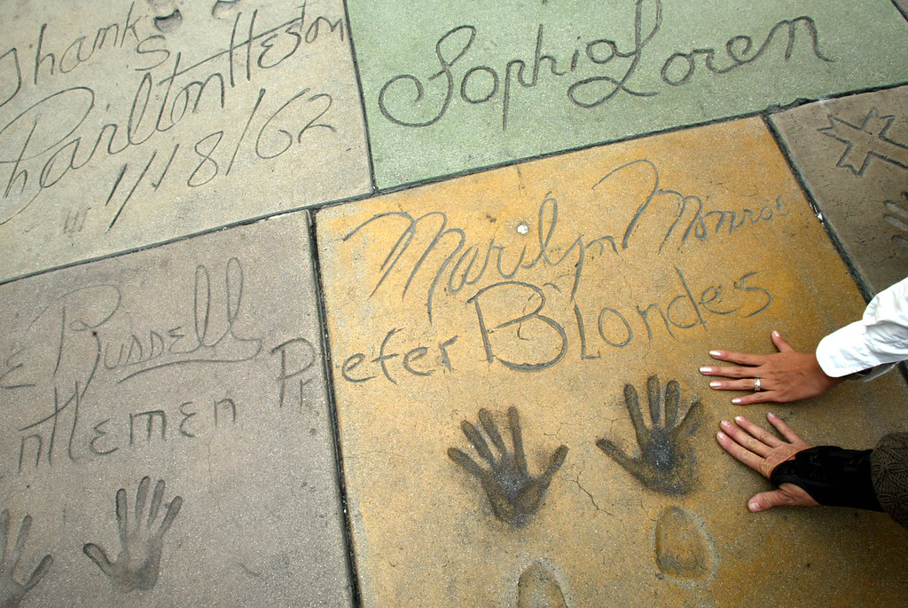 . Tourists place their hands on a cement plaque depicting the hands and shoes of Marilyn Monroe at Chinese Theatre in Hollywood 24 October, 2002. The movie palace was built by cinema impresario Sid Grauman in 1927. The custom of the concrete slabs came about when Grauman accidentally step into  wet cement in the courtyard of the theater, or so the legend goes. (HECTOR MATA/AFP/Getty Images)