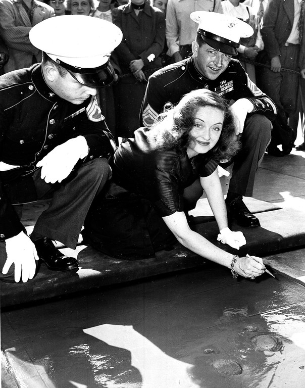 . Actress Bette Davis places her signature in a cement square in the forecourt of Grauman\'s Chinese Theater in Hollywood, Calif., Nov. 6, 1950.  With her are two U.S. Marines, Staff Sgt. Jack Spencer, left, and Tech. Sgt. Bert Nave, right.  The Marines assisted Ms. Davis as a tribute to her work as president of the Hollywood canteen during World War II.  (AP Photo)