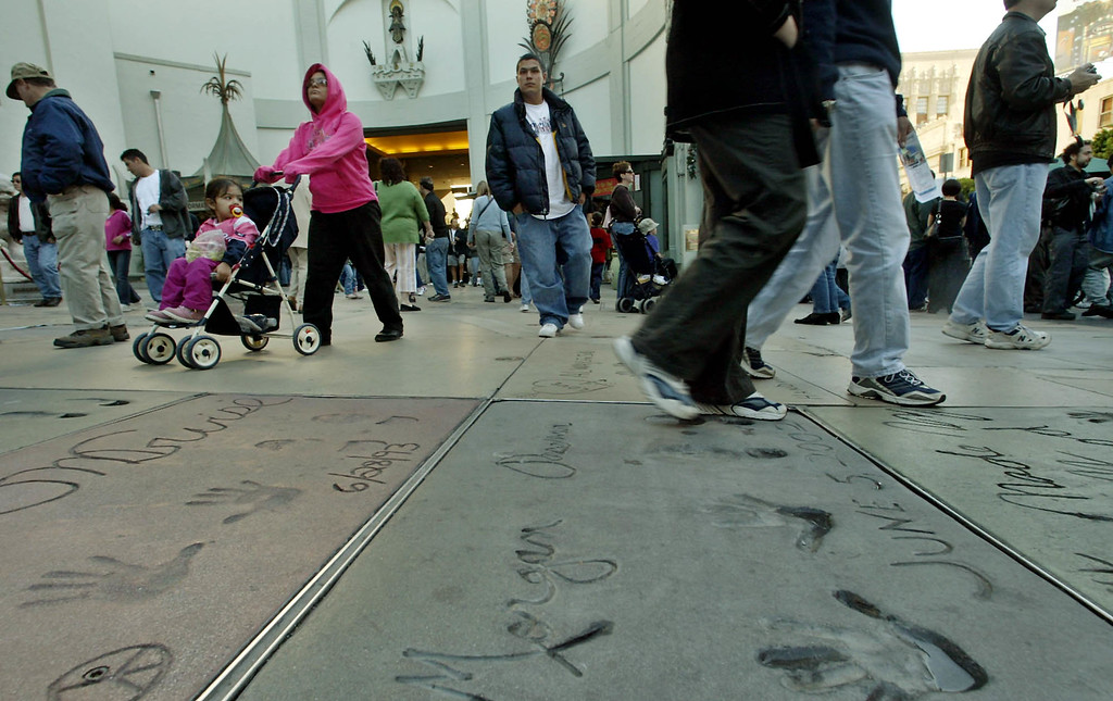 . Alyssa Rodriguez, with Leila, 2, in stroller, and her husband Pablo, center, are warmly dressed as they tour the forecourt at Grauman\'s Chinese Theatre, which features celebrity hand/footprints, Monday, Nov. 29, 2004, in the Hollywood section of Los Angeles.  (AP Photo/Ric Francis)