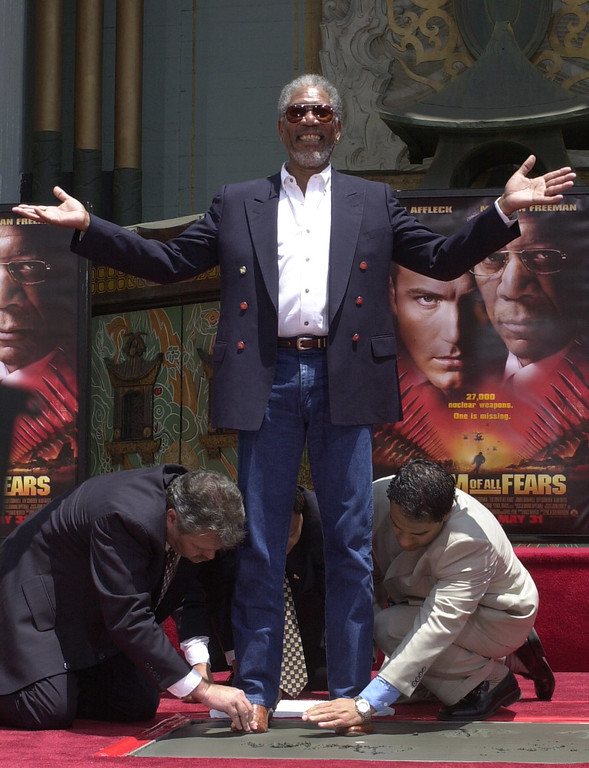 . Actor Morgan Freeman smiles as he gets help putting his feet in cement during a hand and foot print ceremony honoring him Wednesday, June 5, 2002, at Grauman\'s Chinese Theater in the Hollywood section of Los Angeles.  (AP Photo/Nick Ut)