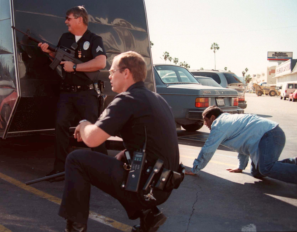 . Los Angeles Police and one civilian take cover behind vehicles as bank robbers are confronted at a Bank of America in the North Hollywood section of Los Angeles Friday, Feb. 28, 1997. Two of the robbers were killed and at least 11 people injured as the robbers opened fire on police and civilians with automatic weapons.  (Photo by Gene Blevins/Los Angeles Daily News)