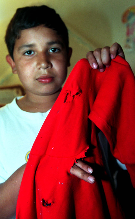 . Victor Gonzalez, 10, shows where shots ripped his sweat shirt as it lay on a night stand in a North Hollywood home. (Los Angeles Daily News file photo)