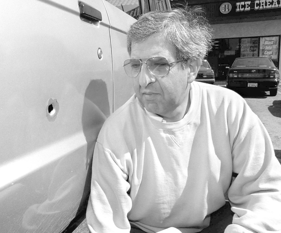 . Serge Sahakians, owner of Mr. Jiffy\'s Pizza, across the street from Bank of America, inspects a bullet hole in his vehicle.  (Los Angeles Daily News file photo)