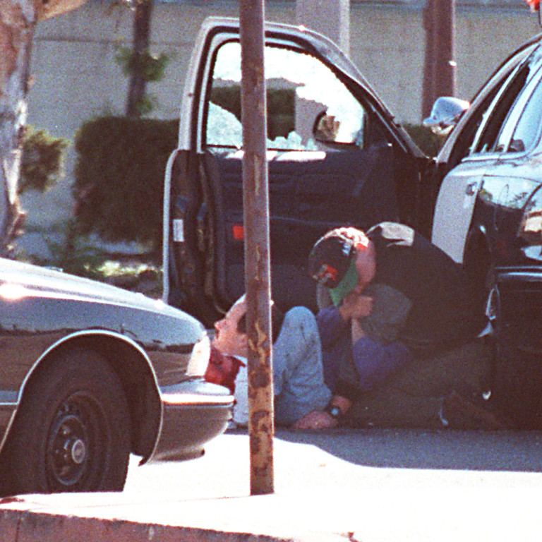 . Taking cover behind a patrol car, a woman is shielded by one man as another man lies wounded after being shot in the arm on Friday, February 28, 1997.  (Photo by Gene Blevins Los Angeles Daily News)