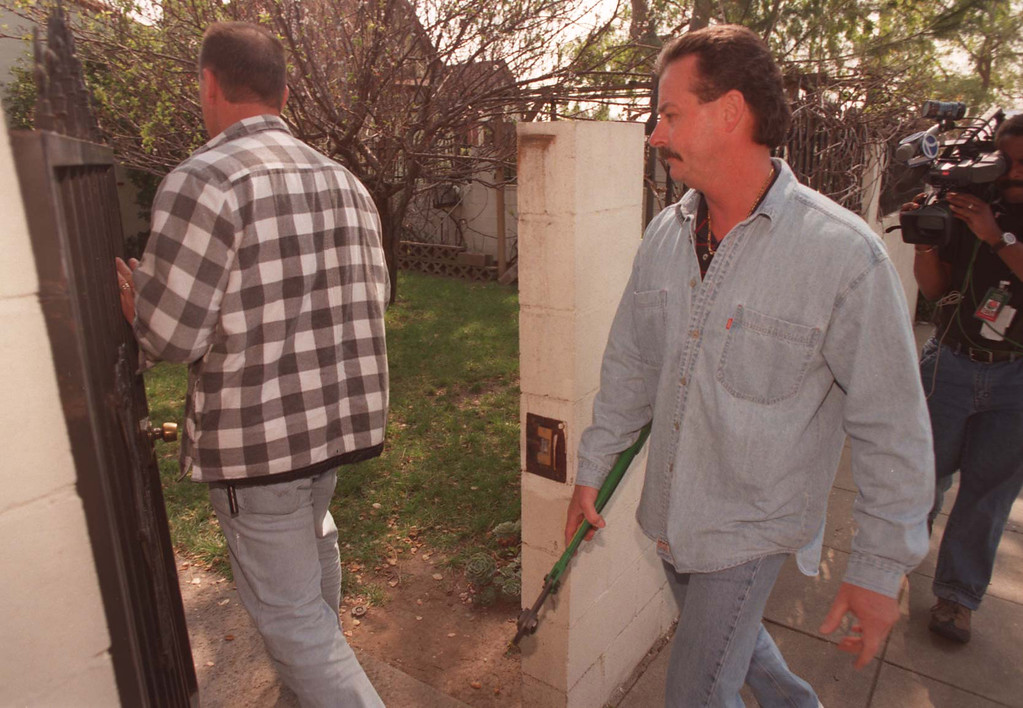 . With bolt cutters and search warrants, police investigators enter the Altadena home where the mother of Emil Matasareanu lives.  (Los Angeles Daily News file photo)
