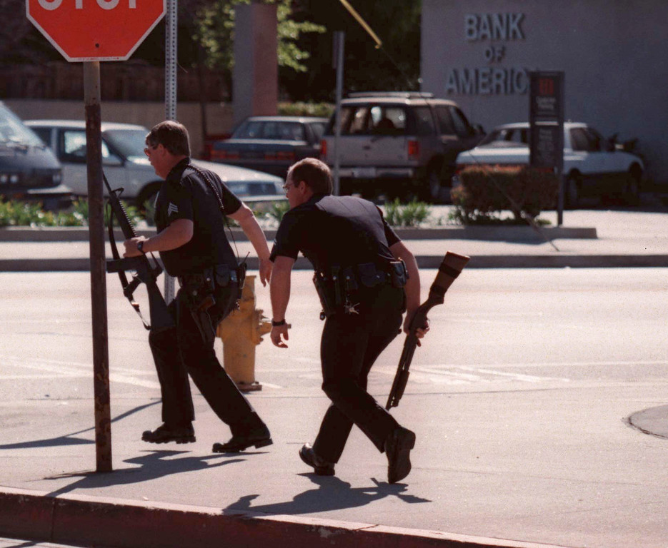 . Bearing shotguns and assault rifles, officers manuever around the scene of the shootout Friday, February 28, 1997.  (Photo by Gene Blevins/Los Angeles Daily News)