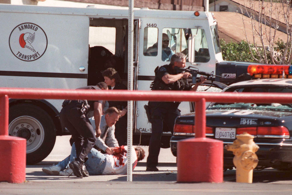 . LAPD officers and SWAT team members use a commandeered armored transport to rescue a wounded man, under fire from a robber at the Bank of America across the street on Friday, February 28, 1997. (Gene Blevins/Los Angeles Daily News)