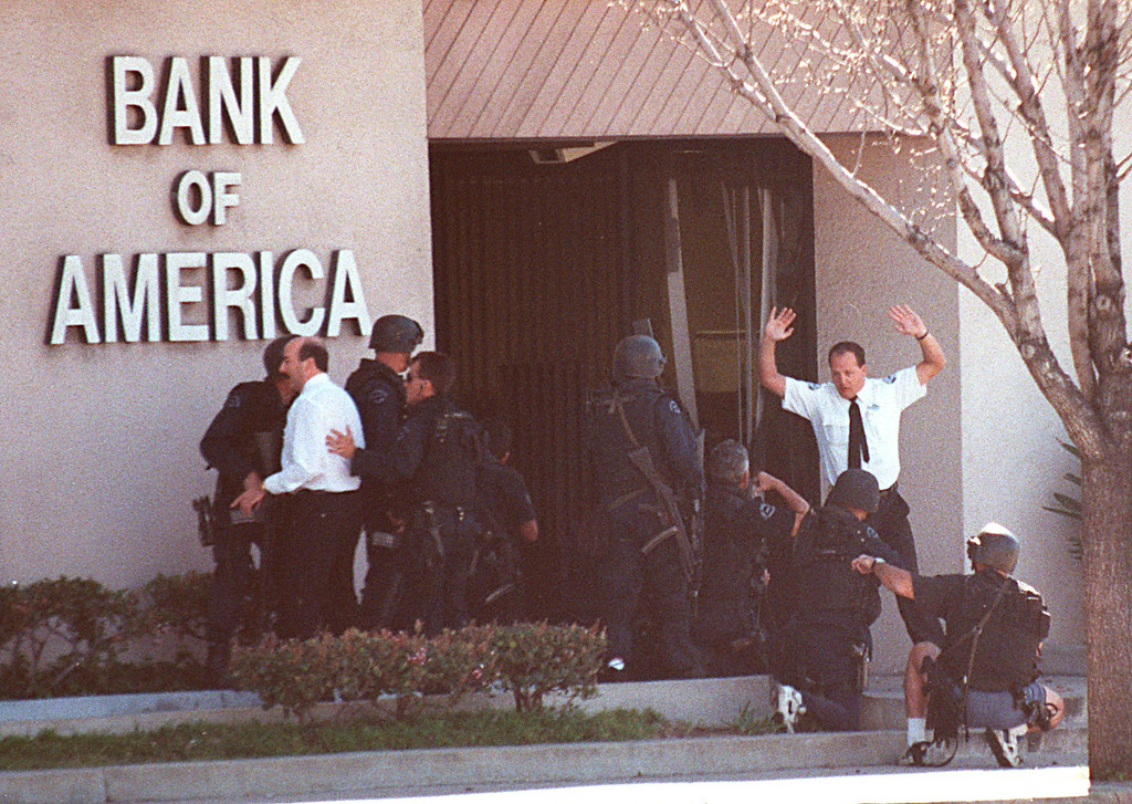 . A bank employee holds up his hands as Los Angeles Police and SWAT units search for more robbery suspects inside the Bank of America in the North Hollywood section of Los Angeles Friday, Feb. 28, 1997. Two of the robbers were killed and at least 11 other people wounded in the wild shootout. (Gene Blevins/Los Angeles Daily News)