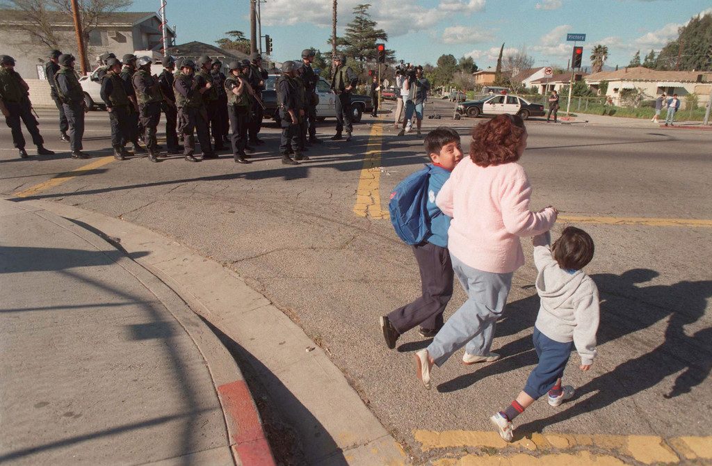 . A mother escorts her children away from Victory Boulevard School, while heavily armed and armored police prepare to search for a possible suspect at large, above. (Daily News file photo)
