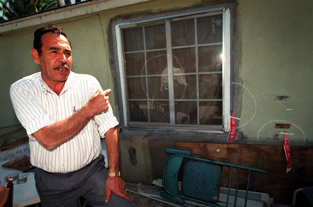 . North Hollywood resident Nubar Torossian points to the bullet holes left on his Archwood Street house after the shootout. (Los Angeles Daily News file photo)