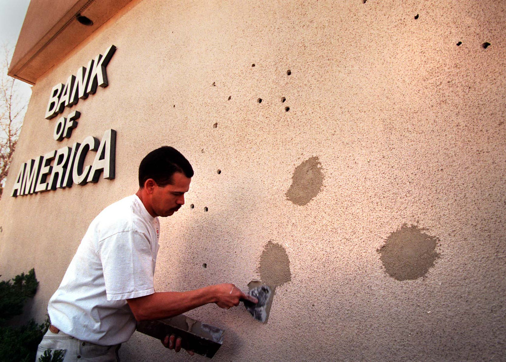 . Antonio Lopez patches bullet holes Saturday, March 1, 1997,  in the wall of the bank where robbers exchanged gunfire with police the day before.  (Los Angeles Daily News file photo)