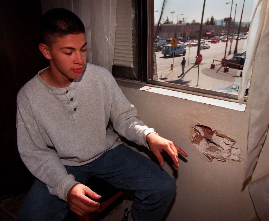 . Eric Gonzalez of Baldwin Park shows bullets he pulled from the walls of the apartments he was visiting across the street fron the Bank of America branch.  (Los Angeles Daily News file photo)