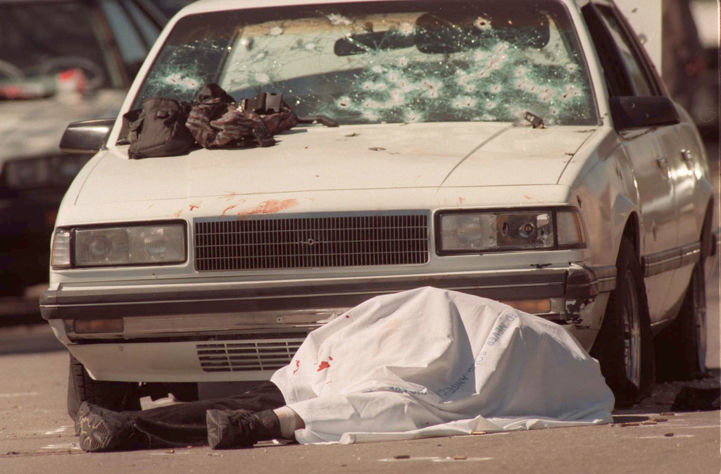 . A bank robber lies dead in front of a car peppered with bullet holes during a botched bank robbery and subsequent shootout in the North Hollywood section of Los Angeles Friday, Feb. 28, 1997. One other robber died and at least 11 people were injured in the shootout. (Hans Gutknecht/Los Angeles Daily News)