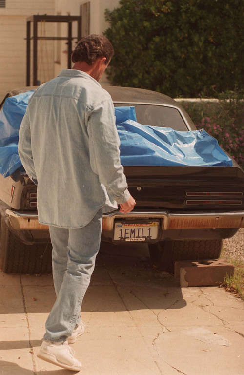 . A search team member combs the yard around the gunman\'s car.  (Los Angeles Daily News file photo)