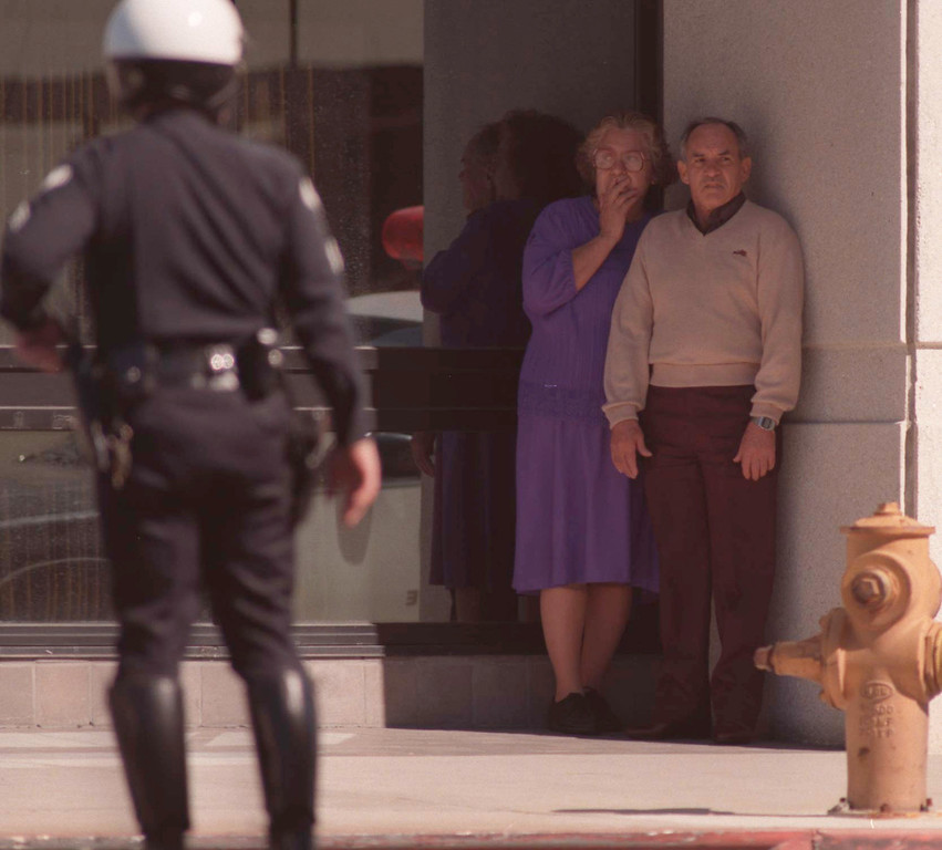 . A couple cowers in a doorway Friday, February 27, 1997, as police clear the intersection of Victory and Laurel Canyon boulevards. (Los Angeles Daily News file photo)