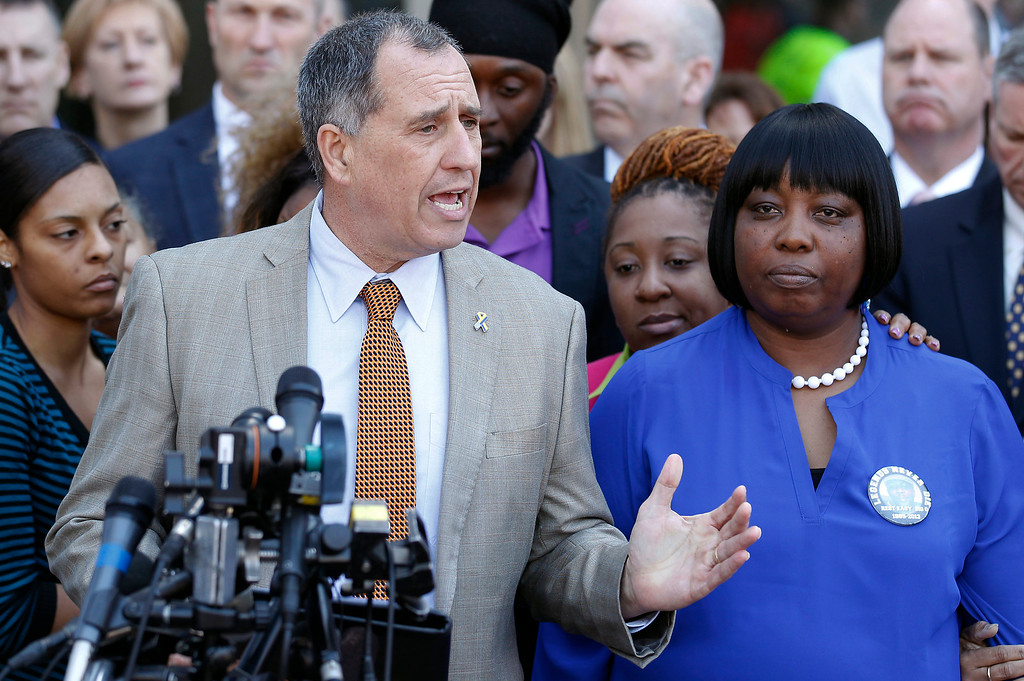 . Acting District Attorney Thomas Quinn, left, answers questions from the media as Ursula Ward, right, mother of slain Odin Lloyd, listens outside Bristol County Superior Court Wednesday, April 15, 2015, in Fall River, Mass., after former New England Patriots football player Aaron Hernandez was found guilty of murder in the shooting death of Odin Lloyd. (AP Photo/Stew Milne)